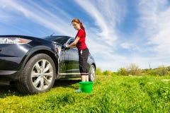 Frau, die schwarzes Auto auf dem Gebiet mit seifigem Schwamm wäscht Stockbilder