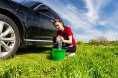 Frau, die schwarzes Auto auf dem Gebiet mit seifigem Schwamm wäscht Lizenzfreie Stockfotos