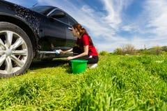 Frau, die schwarzes Auto auf dem Gebiet mit seifigem Schwamm wäscht Lizenzfreies Stockfoto