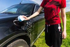 Frau, die schwarzes Auto auf dem grünen Gebiet wäscht Stockbild