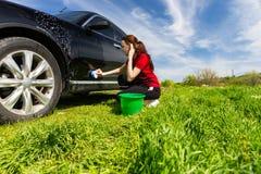 Frau, die schwarzes Auto mit Schwamm auf dem grünen Gebiet wäscht Stockfoto