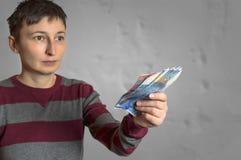 Frau, die Schweizer Franken in der Hand hält Stockbild