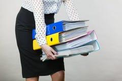 Frau, die schwere bunte Mappen mit Dokumenten hält Stockfoto
