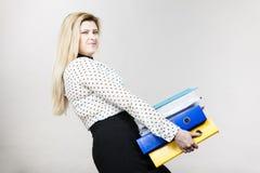 Frau, die schwere bunte Mappen mit Dokumenten hält Lizenzfreie Stockfotos