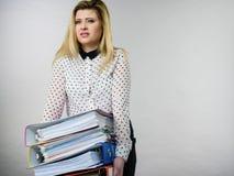 Frau, die schwere bunte Mappen mit Dokumenten hält Stockbild