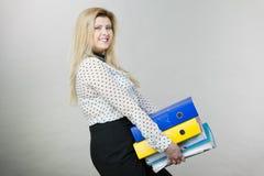Frau, die schwere bunte Mappen mit Dokumenten hält Stockfotos