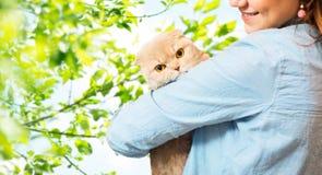 Frau, die Scottishfaltenkatze über Baum hält Lizenzfreie Stockfotos