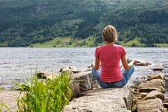 Frau, die am Seeufer sich entspannt Stockfoto