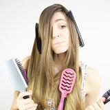 Frau, die sehr lustigen Ausdruck mit Kämmen und Bürsten in ihrem langen Haar macht Lizenzfreie Stockfotos