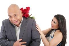 Frau, die sein boysfriend mit einem Blumenstrauß von roten Rosen schlägt. lizenzfreie stockfotos