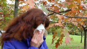 Frau, die seine Nase am Herbstpark durchbrennt stock footage