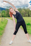 Frau, die Seitenausdehnungen tuend trainiert Stockfotos
