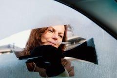 Frau, die Seitenfenster ihres Autos ausrangiert lizenzfreies stockbild