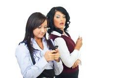 Frau, die seitlich ihrem Freundtelefon betrachtet Stockfotos