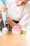 Frau, die mit Sahne selbst gemachte kleine Kuchen verziert Lizenzfreie Stockbilder