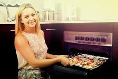 Frau, die selbst gemachte Pizza backt Lizenzfreies Stockfoto