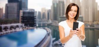 Frau, die selfie durch Smartphone über Dubai-Stadt nimmt Stockfotografie