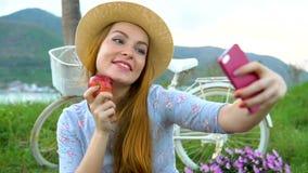 Frau, die selfie mit dem Apfel, Picknick genießend nimmt, stock footage