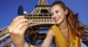 Frau, die selfie mit Digitalkamera gegen Eiffelturm nimmt Lizenzfreie Stockbilder