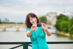 Frau, die selfie mit ihrem Handy auf einer Straße von Paris, Frankreich nimmt Lizenzfreies Stockfoto