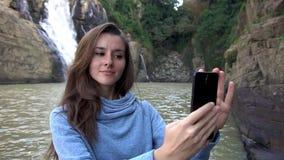 Frau, die selfie mit ihrem Smartphone nahe Wasserfall in Dalat, Vietnam nimmt stock video
