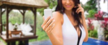 Frau, die selfie mit Smartphone über Bungalow nimmt Stockbild