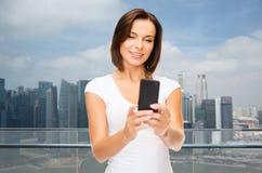 Frau, die selfie mit Smartphone über Singapur nimmt Lizenzfreie Stockfotografie