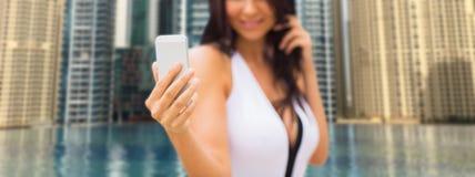 Frau, die selfie mit Smartphone über Stadtpool nimmt Stockbilder