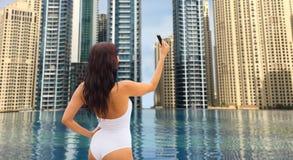 Frau, die selfie mit Smartphone über Stadtpool nimmt Stockbild