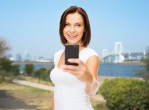 Frau, die selfie mit Smartphone über Tokyo nimmt Stockfotografie