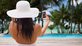 Frau, die selfie mit Smartphone auf Strand nimmt Stockbild