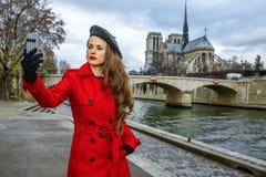 Frau, die selfie mit Telefon nahe Notre Dame de Paris in Paris nimmt Stockfotos