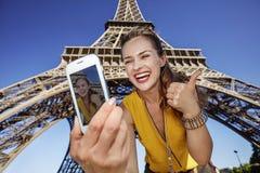 Frau, die selfie mit Telefon vor Eiffelturm in Paris nimmt Stockbilder