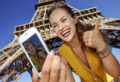 Frau, die selfie mit Telefon vor Eiffelturm in Paris nimmt Stockbild