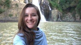 Frau, die selfie nahe Wasserfall in Dalat, Vietnam nimmt stock video