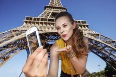 Frau, die selfie nimmt und Luftkuß nahe Eiffelturm durchbrennt Lizenzfreie Stockbilder
