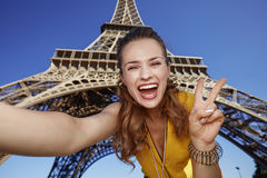 Frau, die selfie nimmt und Sieg gegen Eiffelturm zeigt Stockfoto