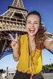 Frau, die selfie nimmt und Sieg gegen Eiffelturm zeigt Stockbilder