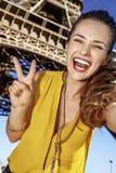 Frau, die selfie nimmt und Sieg gegen Eiffelturm zeigt Stockbild