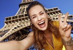 Frau, die selfie nimmt und Sieg gegen Eiffelturm zeigt Stockfotografie