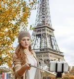 Frau, die selfie unter Verwendung selfie Stockes auf Damm in Paris nimmt Lizenzfreie Stockfotos