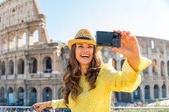 Frau, die selfie vor colosseum in Rom macht Stockbilder