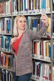 Frau, die Selfies am Telefon in der Bibliothek nimmt Lizenzfreie Stockbilder