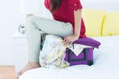 Frau, die sich auf ihren Koffer hinsetzt Lizenzfreie Stockfotos