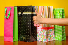 Frau, die sich Daumen zeigt Konzepterfolg, Einkaufstaschen auf dem Hintergrund Stockbild