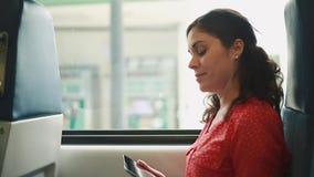 Frau, die sich in der Hand innerhalb von einem Zug/eines Busses mit einem Tablet-Computer hinsetzt stock footage