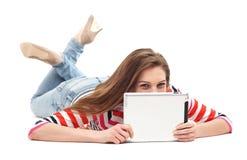 Frau, die sich mit digitaler Tablette hinlegt Stockbild