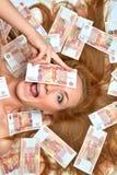 Frau, die sich mit viele rubl Russe des Bargelds fünf tausend hinlegt Stockbilder