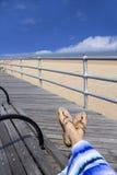 Frau, die sich nah auf Strand, Füße in den Sandalen oben entspannt Stockfoto