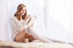 Frau, die sich zu Hause auf Buch des Bodens Leseentspannt Stockbilder